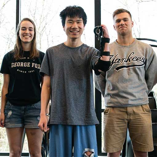 Evan Bonazzola wearing his new prosthetic holding it up to the camera. Two George Fox students stand behind him.