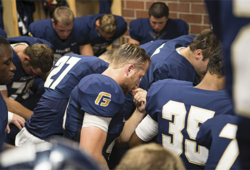 Players bow their heads for a pregame prayer – a quiet moment before being welcomed on the field by a roaring crowd.