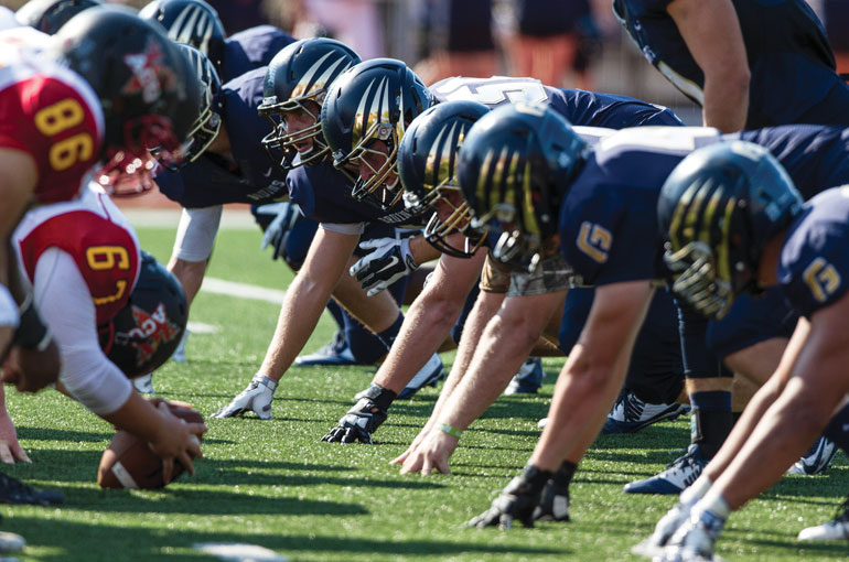 George Fox defenders line up in the trenches, ready to scuff up their shiny new helmets created by HGI – the same company that designs helmets for the Oregon Ducks and Seattle Seahawks.