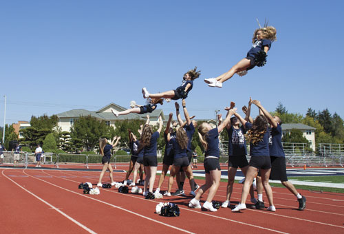 The cheerleading squad keeps the student section entertained with some aerial acrobatics during a stoppage in play.