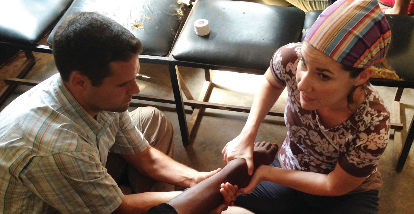 Physical therapy students Ryan MacKenzie and Lauren Bennett evaluate a patient's foot at an adult clinic just outside Kampala.
