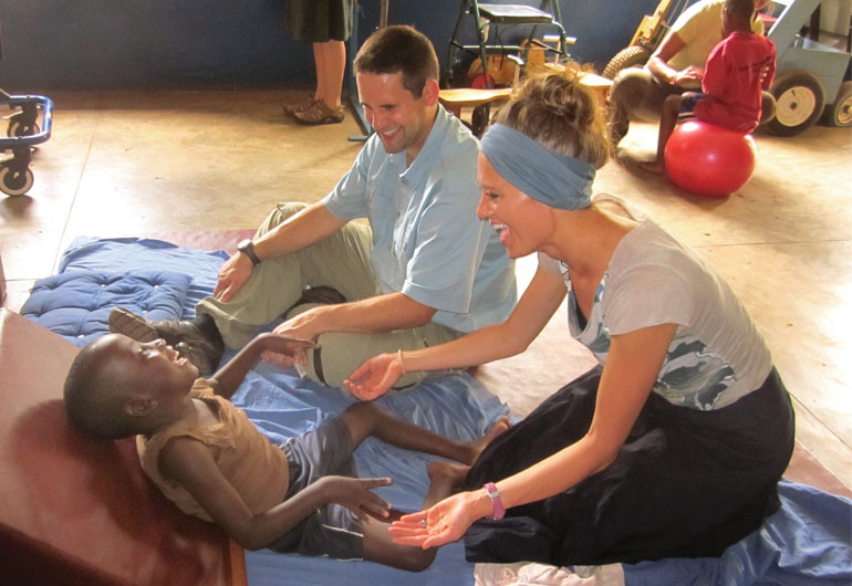 Husband and wife duo Ryan and Lene MacKenzie work on trunk control/strengthening movements and exercises with a young girl.