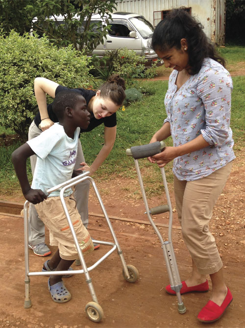 Third-year DPT students Alicia Martinez (left) and Marisol Cardoza assist Ivan, a child with cerebral palsy who attends the School for the Disabled in Kampala, Uganda. Cardoza and Martinez taught the boy how to walk with crutches instead of a wheeled walker.
