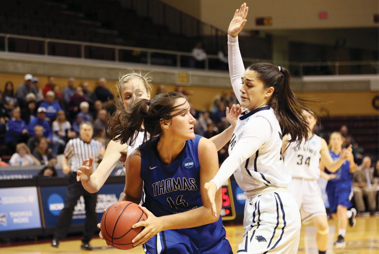 Lauren Codling and Sammy Naluai swarm a Thomas More player during the championship game. Naluai (right) earned the Elite 89 award for having the highest cumulative GPA in the Final Four.